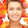 Lovely woman with red flowers - Foto Stock