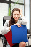 Young businesswoman with folders sitting in chair — Stock Photo