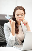 Pensive woman with computer and euro cash money — Stock Photo