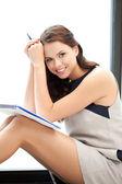 Szczęśliwa kobieta z wielkim notatnik — Zdjęcie stockowe