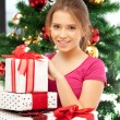 Happy woman with gift box and christmas tree — Stock Photo #7844029