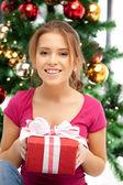 счастливая женщина с подарочной коробке и рождественская елка — Стоковое фото