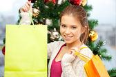Donna felice con borse della spesa e albero di natale — Foto Stock