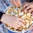 Children eat popcorn out of paper bucket, close-up — Stock Photo #6965273