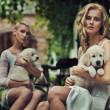 Two cute blondie hugging puppies — Stock fotografie #7064283