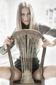 Cute woman sitting on a old chair — Stock Photo