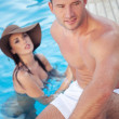 Attractive couple on poolside — Stock Photo