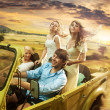 Group of cheerful friends driving a cabriolet — Stok fotoğraf