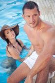 Casal atraente na beira da piscina — Fotografia Stock