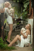 Two beauty ladies with cute puppies — Stock Photo