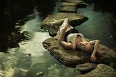 Beautiful lady lying on rocks — Stock Photo