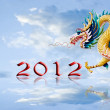 Dragon flying with 2012 year number and nice sky background - Stock Photo