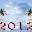 Dragon flying with 2012 year number with sky background - Stock Photo