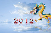 Dragon flying with 2012 year number and nice sky background — Stock Photo
