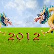 Golden dragon flying over the fields with 2010 year number - Stock Photo