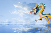 Golden dragon flying over the sea with nice sky background — Stock Photo