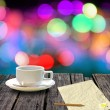 Hot coffee and letter paper on wooden table with colorful bokeh background — Stock Photo