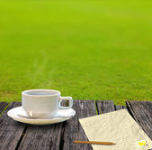 Hot coffee and letter paper on the wooden table with grass garden — Stock Photo