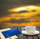 Coffee cup and letter on the wooden table with sunset sky background — Stock Photo