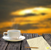 Coffee cup and letter on the wooden table with sunset sky — Stock Photo