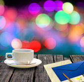 Hot coffee and letter on wooden table with colorful bokeh background — Stock Photo