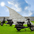 Stock Photo: Black retro scooter with stone road to sun