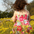 Young girl standing in a field of yellow flowers — Stock Photo