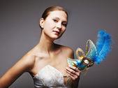 Beautiful young woman wearing blue carnival mask — Stock Photo