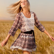 Woman walking on wheat field — Stock Photo #6819324