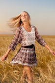 Woman walking on wheat field — Stock Photo
