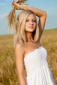 Woman walking on wheat field — Stock Photo