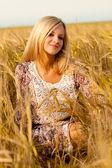 Woman sitting on wheat field — Stock Photo