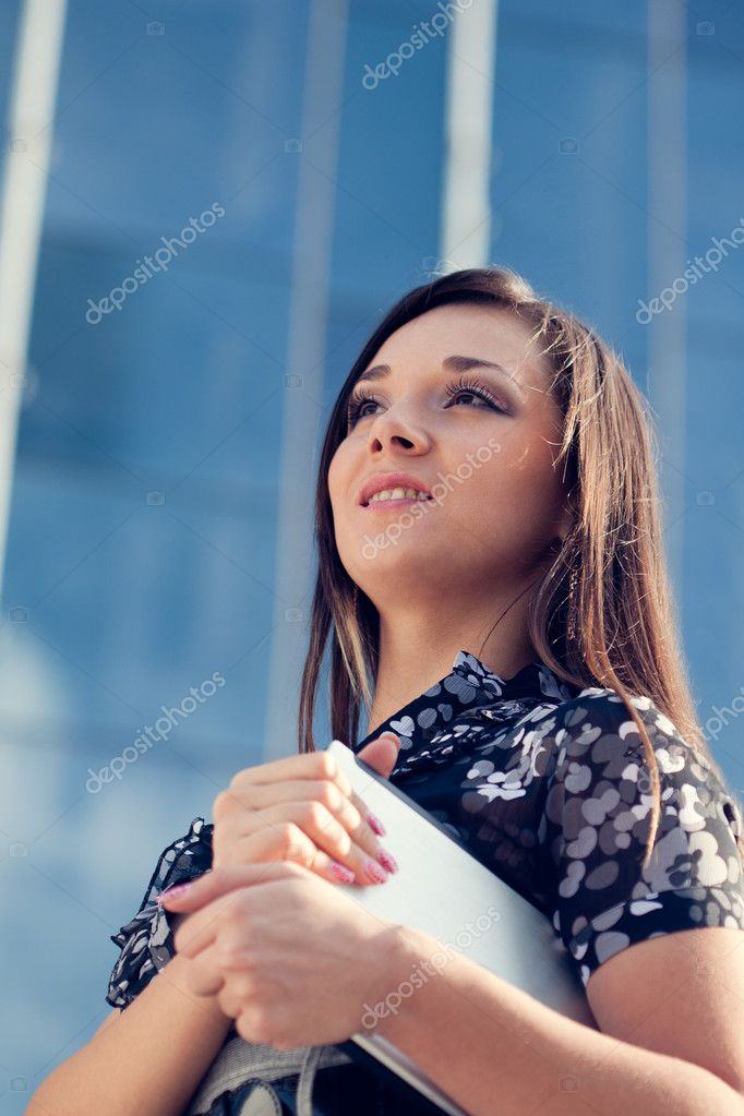 Beautiful woman holding laptop over glass building background, vertical — Stock Photo #7233576