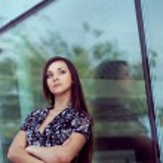 Woman standing near glass wall — Stock Photo