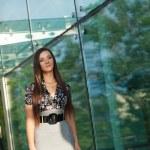 Brunette walking along glass wall — Stock Photo