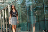 Woman walking along glass wall — Stock Photo