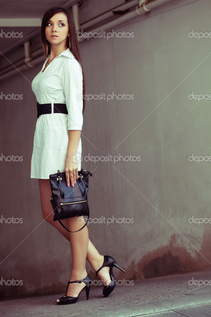 Beautiful brunette woman with clutch looking around, outtdors fashion photo  Stock Photo #7343355