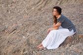 брюнетка сидит на камне — Стоковое фото