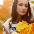 Brunette holding oak leaves — Stock Photo