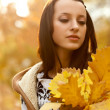 Brunette holding yellow leaves — Stock Photo