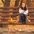 Woman sitting on brown bench - Stock Photo