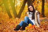 Woman sitting on ground in autmn park — Stock Photo