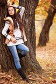 Woman posing near tree in autmn park — Stock Photo