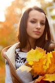 Brunette holding oak leaves — Stock Photo