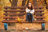 Woman sitting on brown bench — Stock Photo