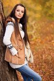 Fashion model standing near tree in autmn park — Stock Photo
