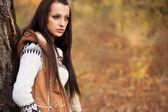 красивая женщина, стоя возле дерево в осень парке — Стоковое фото