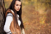 Beautiful woman standing near tree in autmn park — Stock Photo