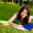 Woman laying on grass and writing — Stock Photo