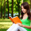 Woman reading book at park - Stock Photo